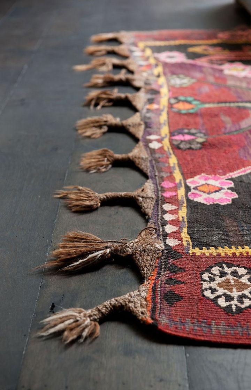detail van franjes bij een rood marokkaans tapijt