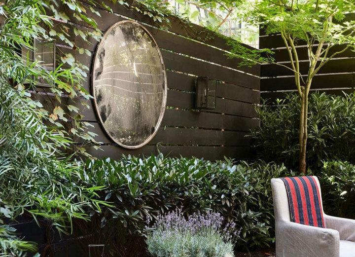 ronde spiegel in tuin tegen schutting