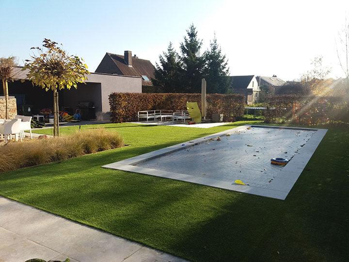 zwembad met kunstgras er rond in tuin