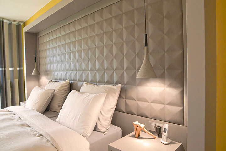 betonnen hanglampen in slaapkamer naast het bed