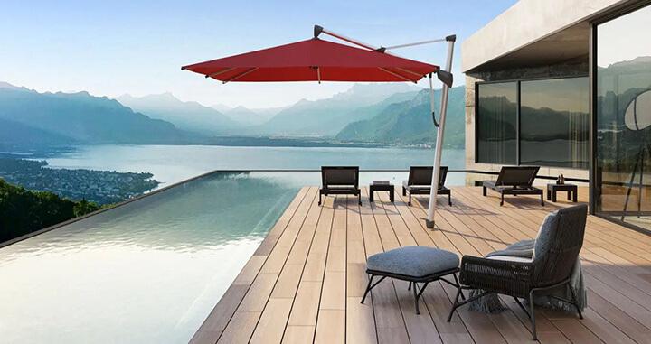 rode parasol op terras naast zwembad