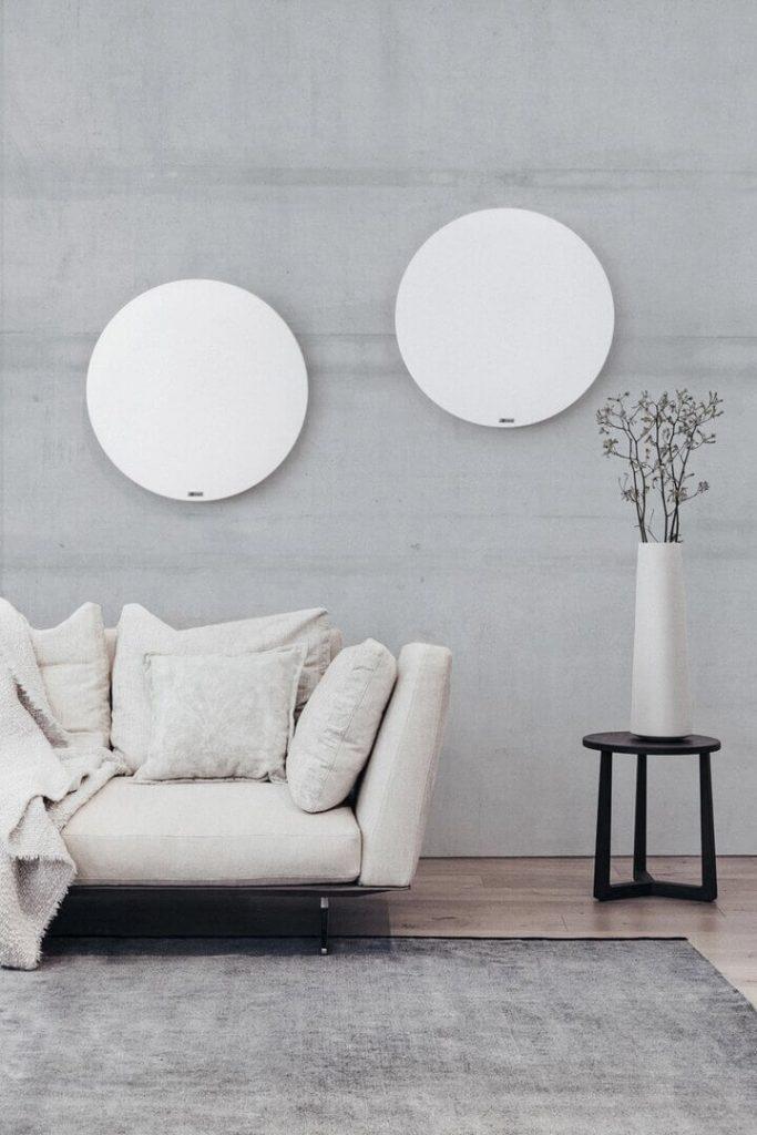 witte ronde panelen voor infraroodverwarming tegen de muur van de woonkamer