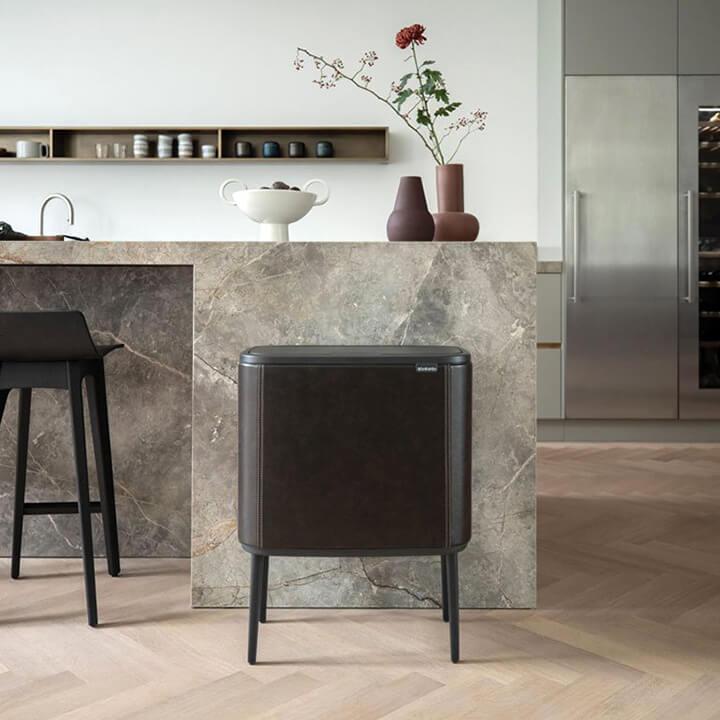 design afvalemmer op pootjes voor stenen keukeneiland