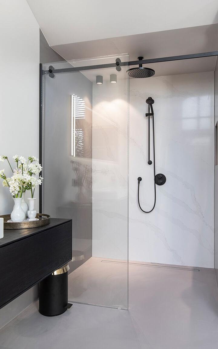 lichte gietvloer in badkamer met inloopdouche en zwart meubel