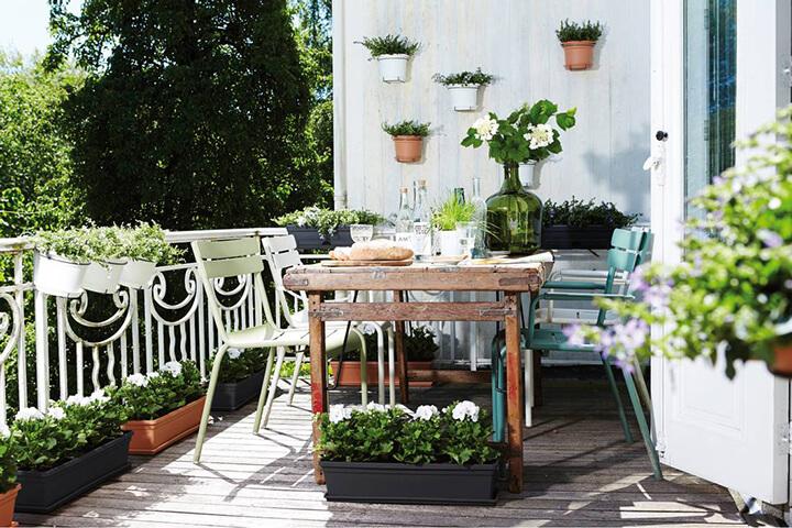 balkon met plantenbakken, tafel en stoelen