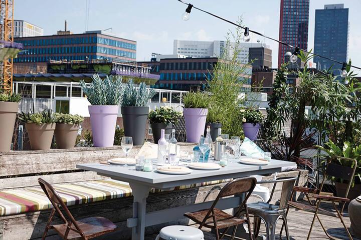 dakterras in de stad met tafels, stoelen, planten en een lichtslinger