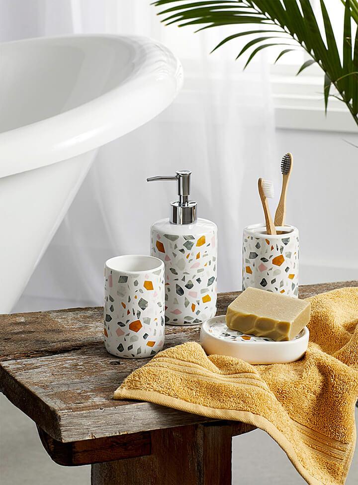 terrazzo badkamer accessoires op houten bankje met mosterd gele handdoek