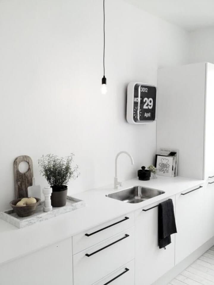 witte moderne keuken met zwarte handgrepen en hanglamp