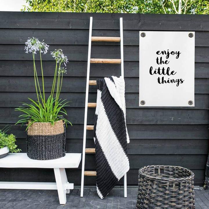 tuinposter tegen zwarte houten tuinafsluiting